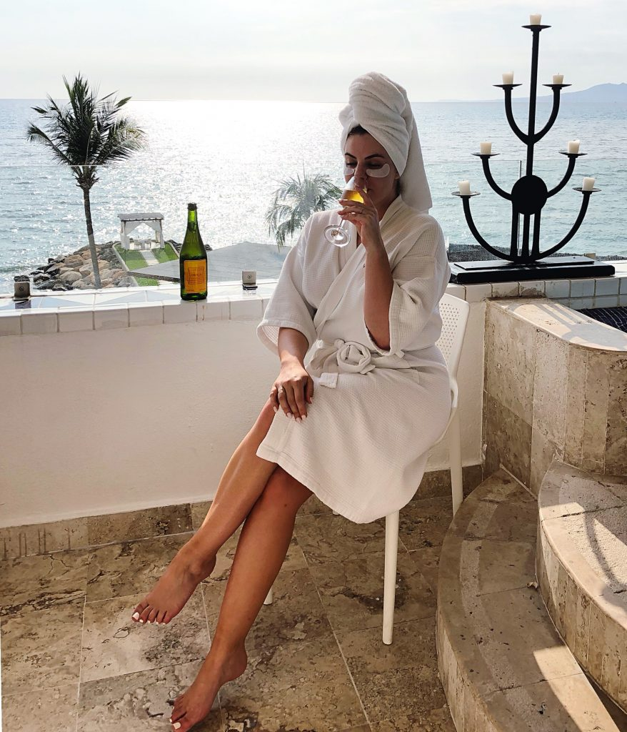 woman in robe drinking champagne